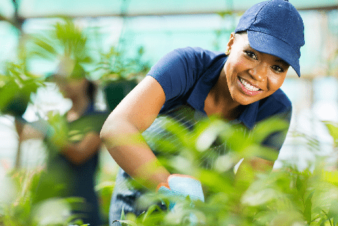 A woman wearing blue cap is smiling while posing for a picture
