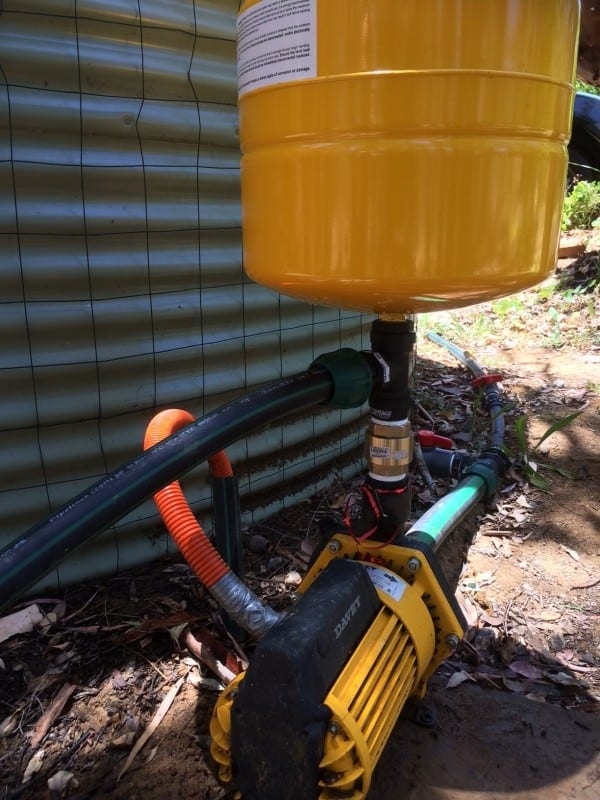 High-quality water pump connected to a yellow colour tank in backyard